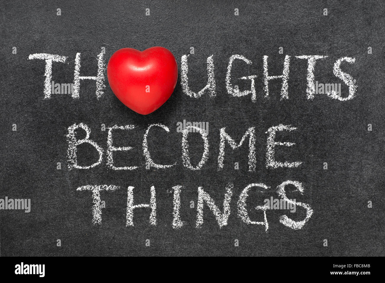 thoughts become things phrase handwritten on blackboard with heart symbol instead O - Stock Image