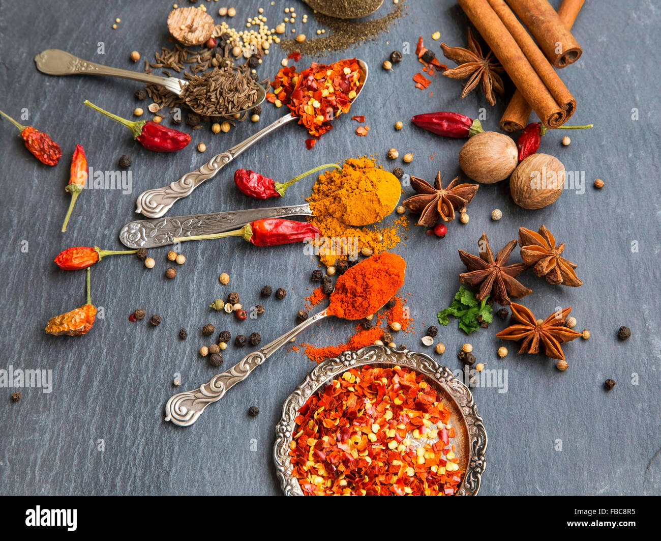 Aromatic spices with pepper and turmeric powders,cumin and coriander seeds, chili flakes , anise, nutmeg and cinnamon - Stock Image