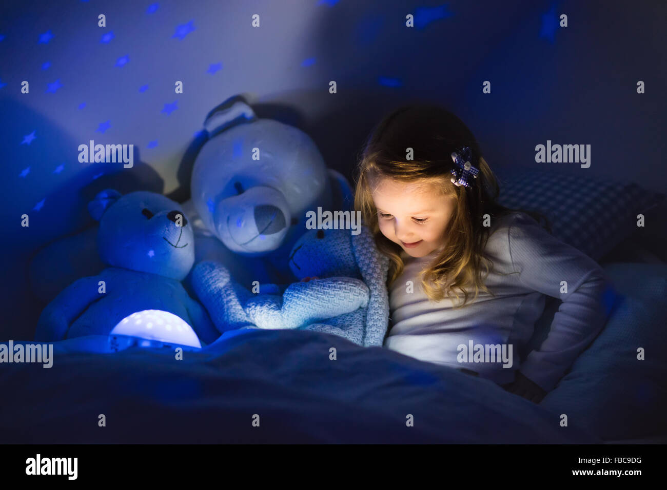 Little Girl Reading A Book In Bed. Dark Bedroom With Night Light Projecting  Stars On Room Ceiling. Kids Nursery And Bedding.