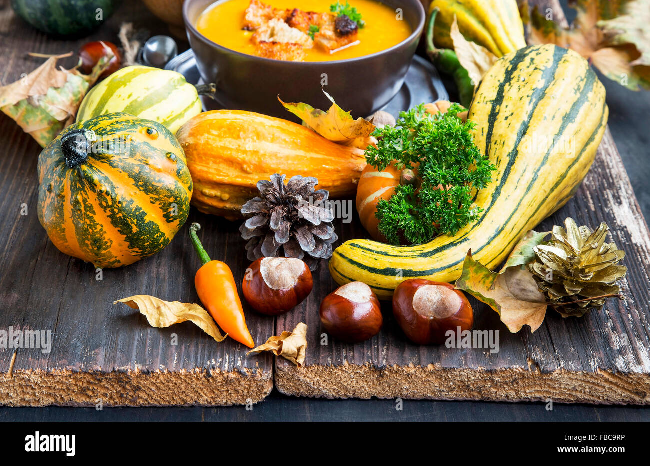 Autumn Decorations with Pumpkins, Dried Leaves, Chestnuts and Acorns in Wooden Background - Stock Image