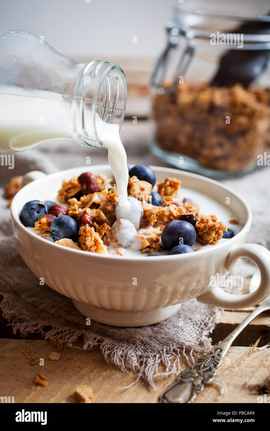 Homemade granola with milk and fresh blueberries - Stock Image