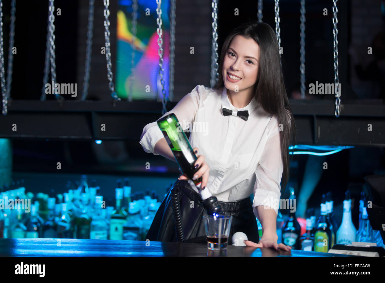 Beautiful cheerful brunette bartender girl in white shirt and black bow tie, serving alcohol drink at bar counter, - Stock Image