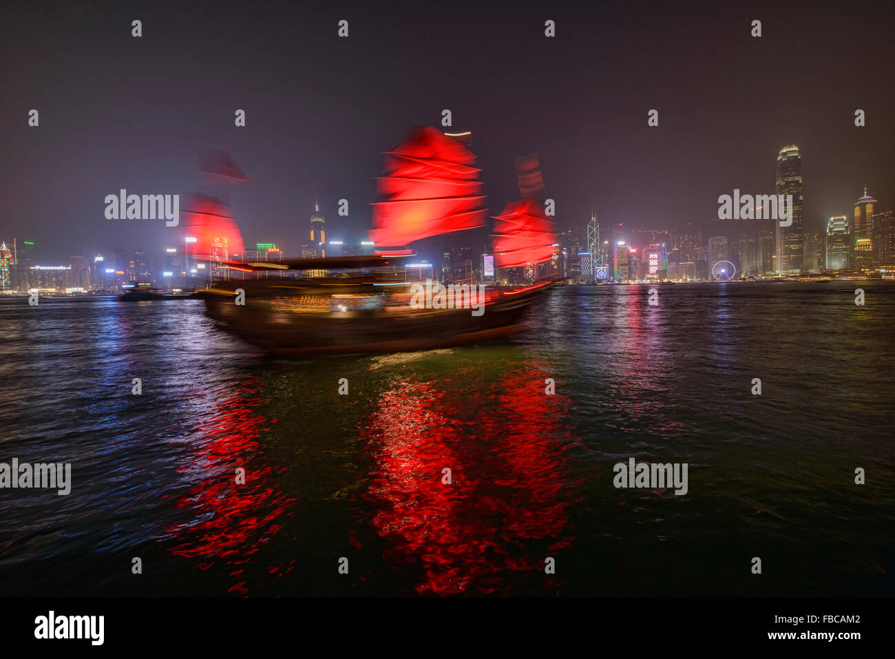 A traditional junk sails through the harbour at night in Hong Kong - Stock Image
