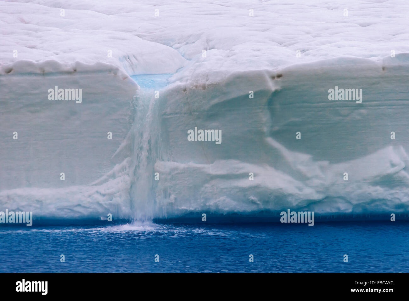 Meltwater flowing from ice wall of melting Brasvellbreen glacier into the Arctic Ocean, Austfonna, Nordaustlandet, - Stock Image