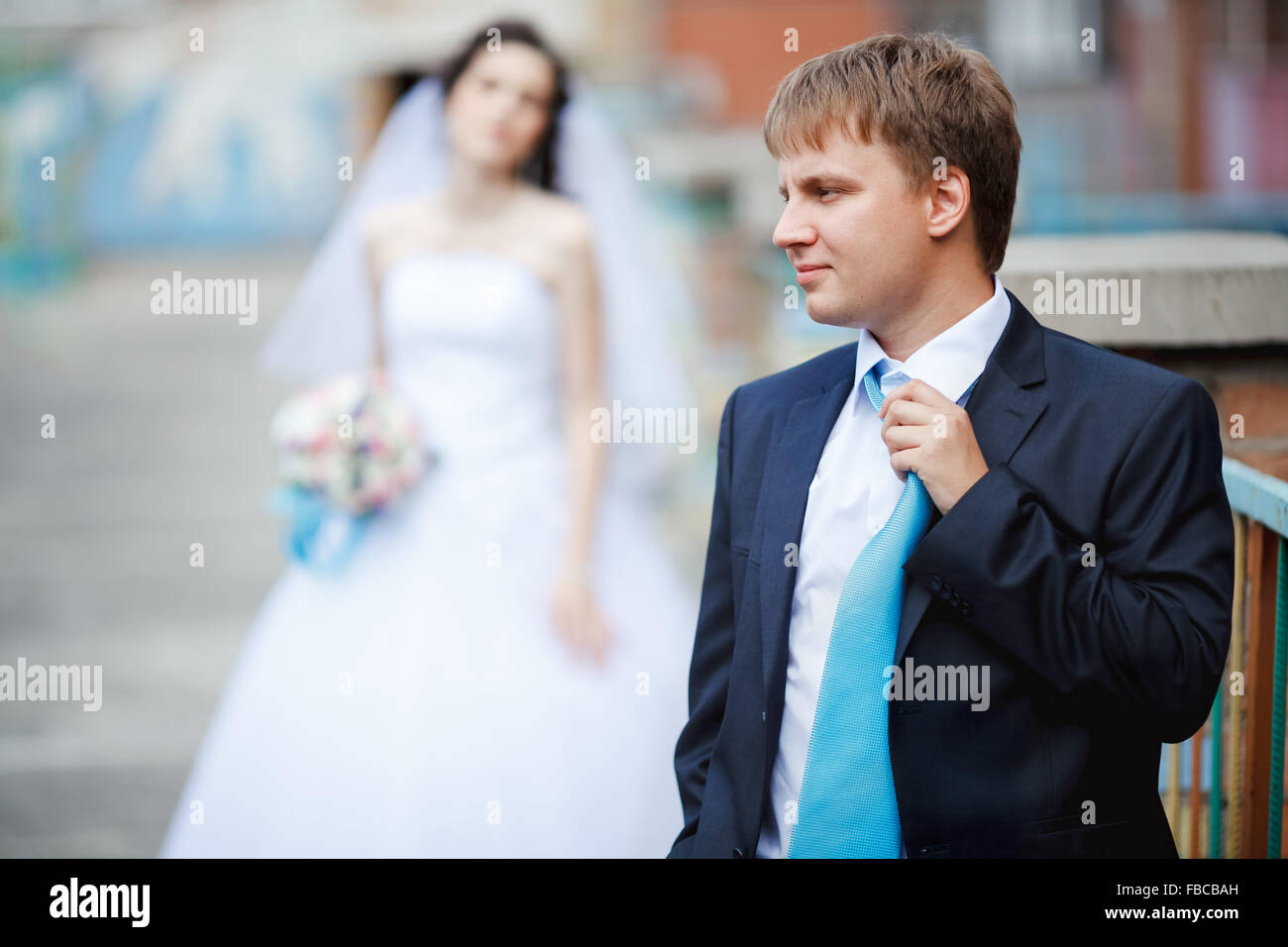 The groom dark blue suit straightens turquoise tie with a sour face, in background tired and frustrated bride waiting. - Stock Image