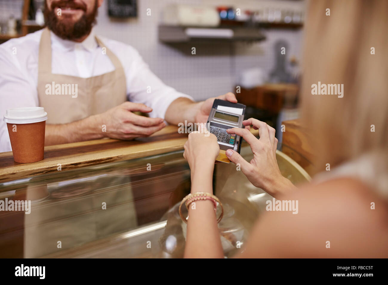 Young woman paying for coffee by credit card at coffee shop. Focus on woman hands entering security pin in credit - Stock Image
