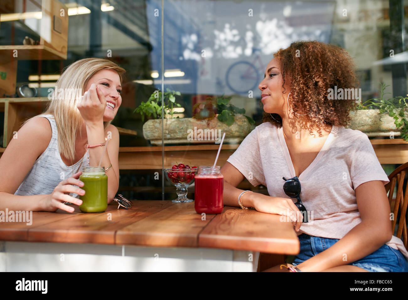 Two happy women sitting in a outdoor restaurant. Female friends enjoying drinks and chat at sidewalk cafe. - Stock Image