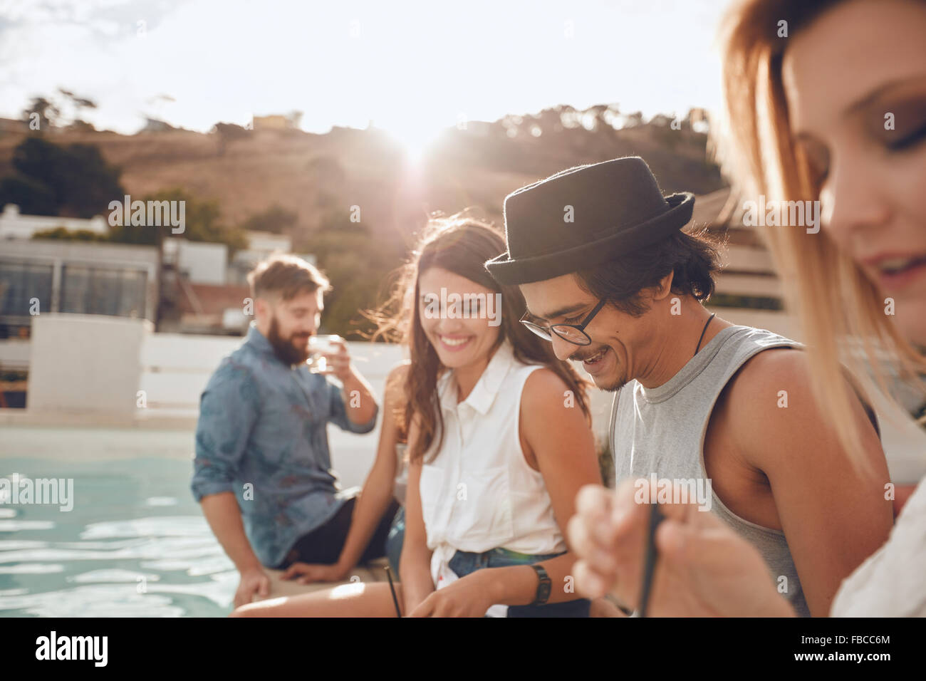 Outdoor shot of happy young man sitting by the pool with his friends partying. Group of young people hanging around Stock Photo