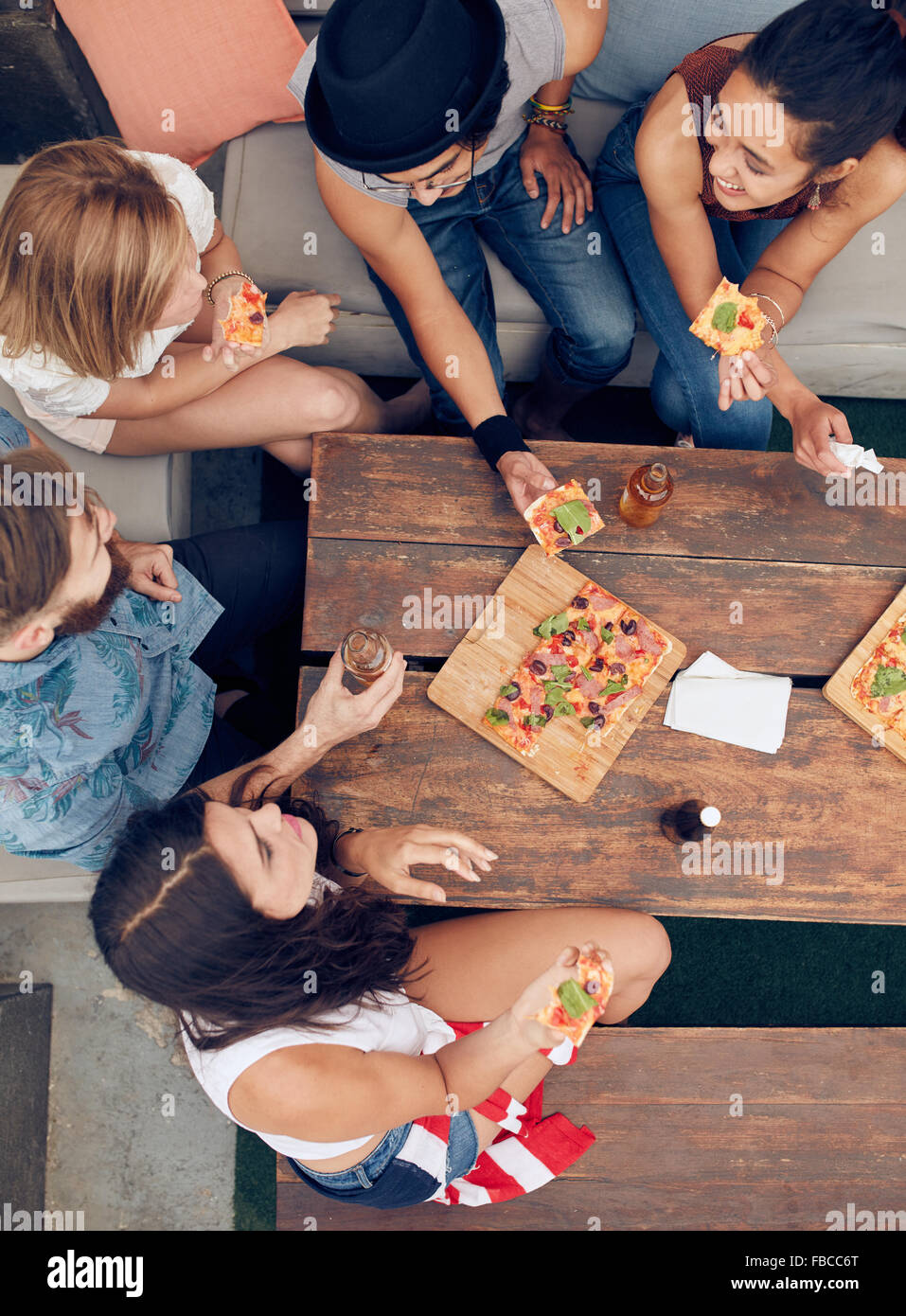 Top view of group of young people having drinks and pizza at party. Multiracial friends hanging out together. Stock Photo