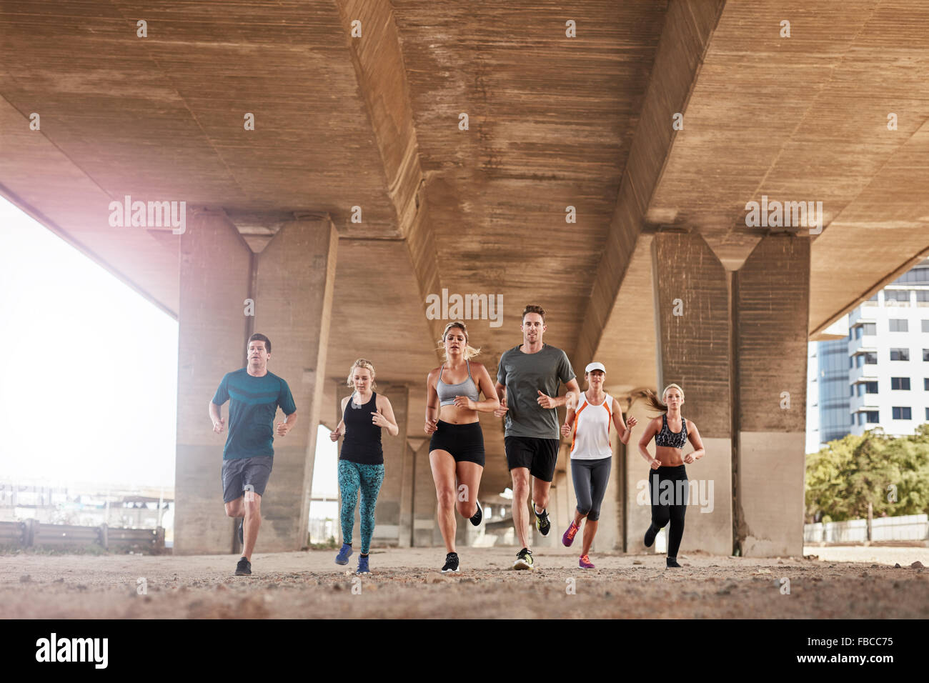 Group of healthy people running under a bridge. They are running in the city wearing sport clothing. - Stock Image