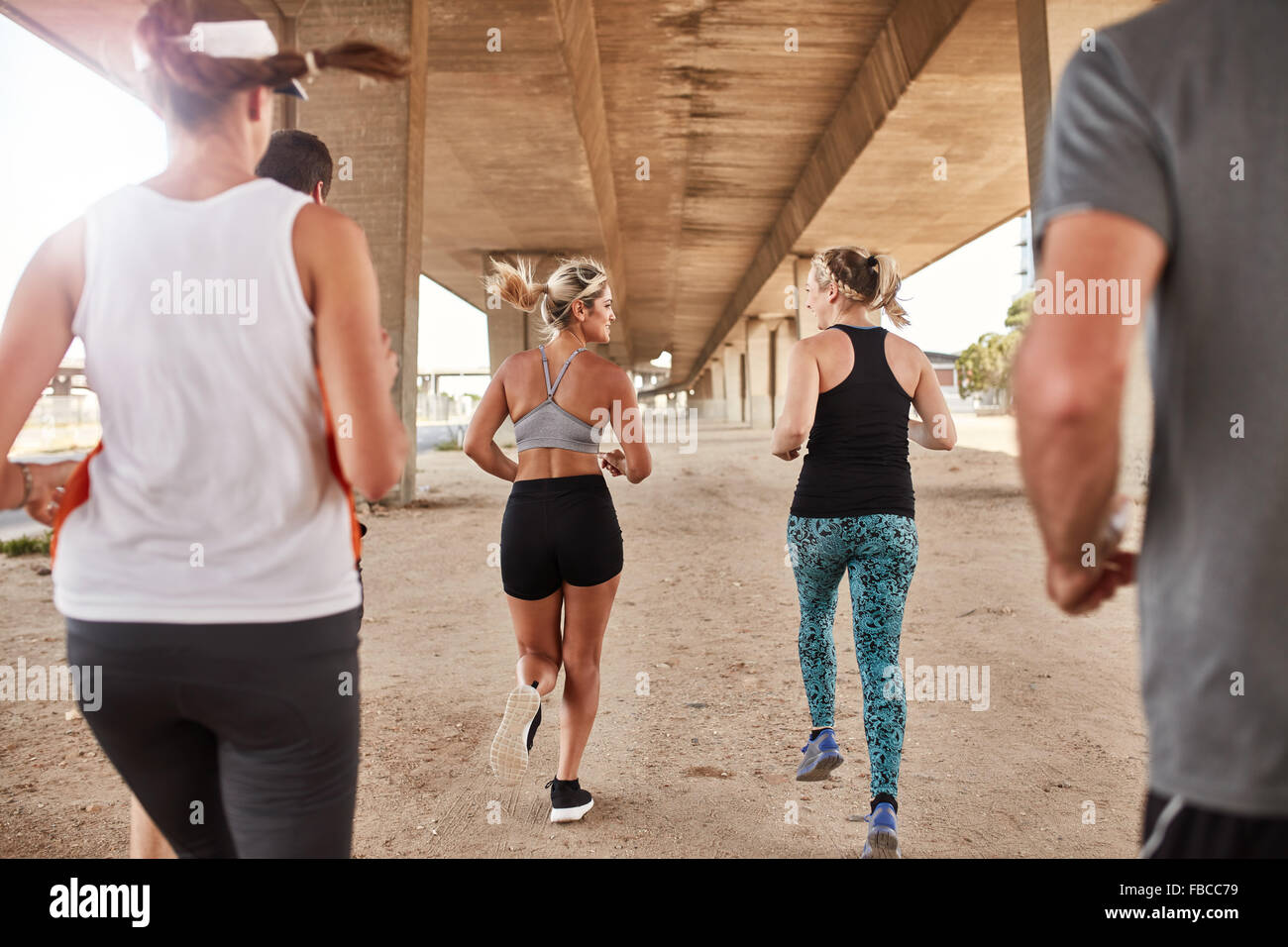 Portrait of group of runners in fitness clothing running under a bridge. Young men and women running together. - Stock Image