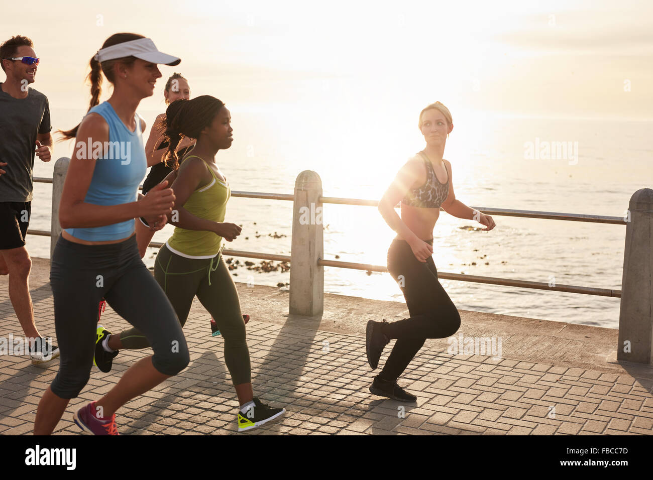 Young people running along seaside at sunset. Closeup image of group of runners working out on a road by the sea. - Stock Image