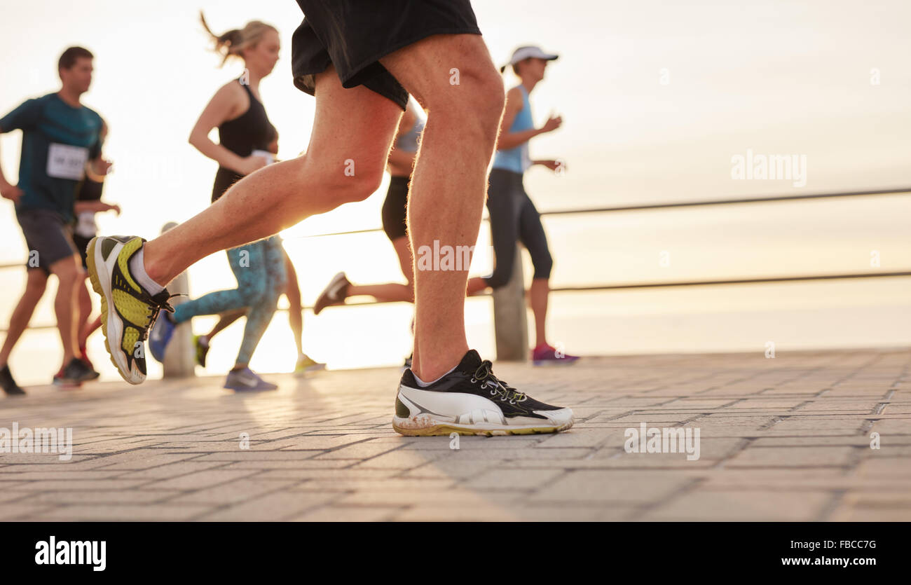 Closeup portrait of people running on road by the sea with focus on feet of male runner. - Stock Image