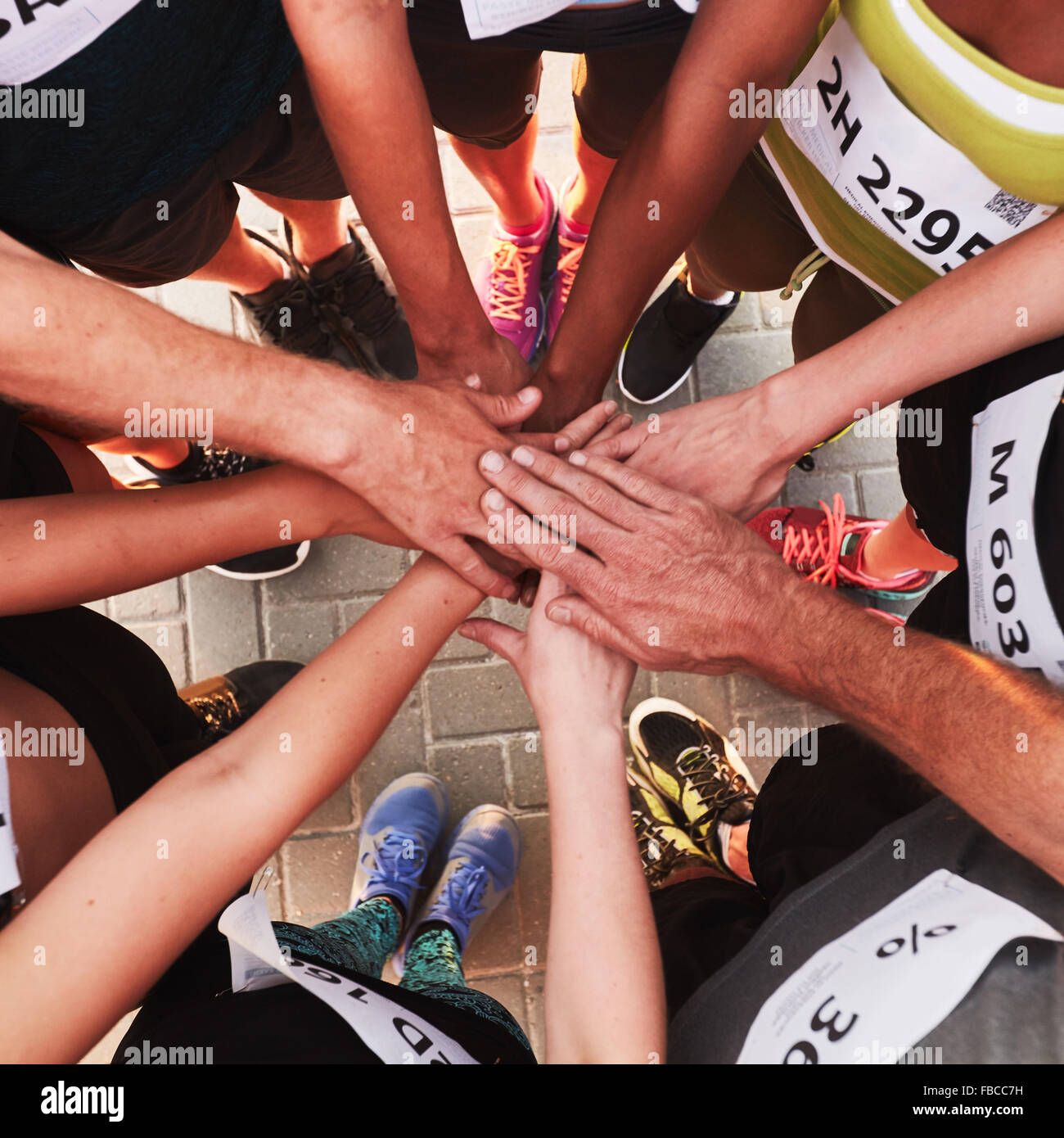 Hands of running team stacked on top of each other. Top view of a sports team standing in a circle with their hands - Stock Image