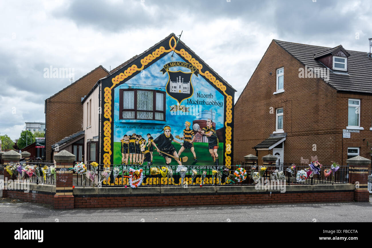 An Irish GAA Hurling and Gaelic football mural in markets area of Belfast with flower tributes to the late Jock Stock Photo