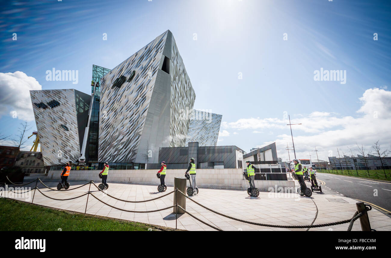 Segway users pass Belfast's iconic Titanic building. Stock Photo