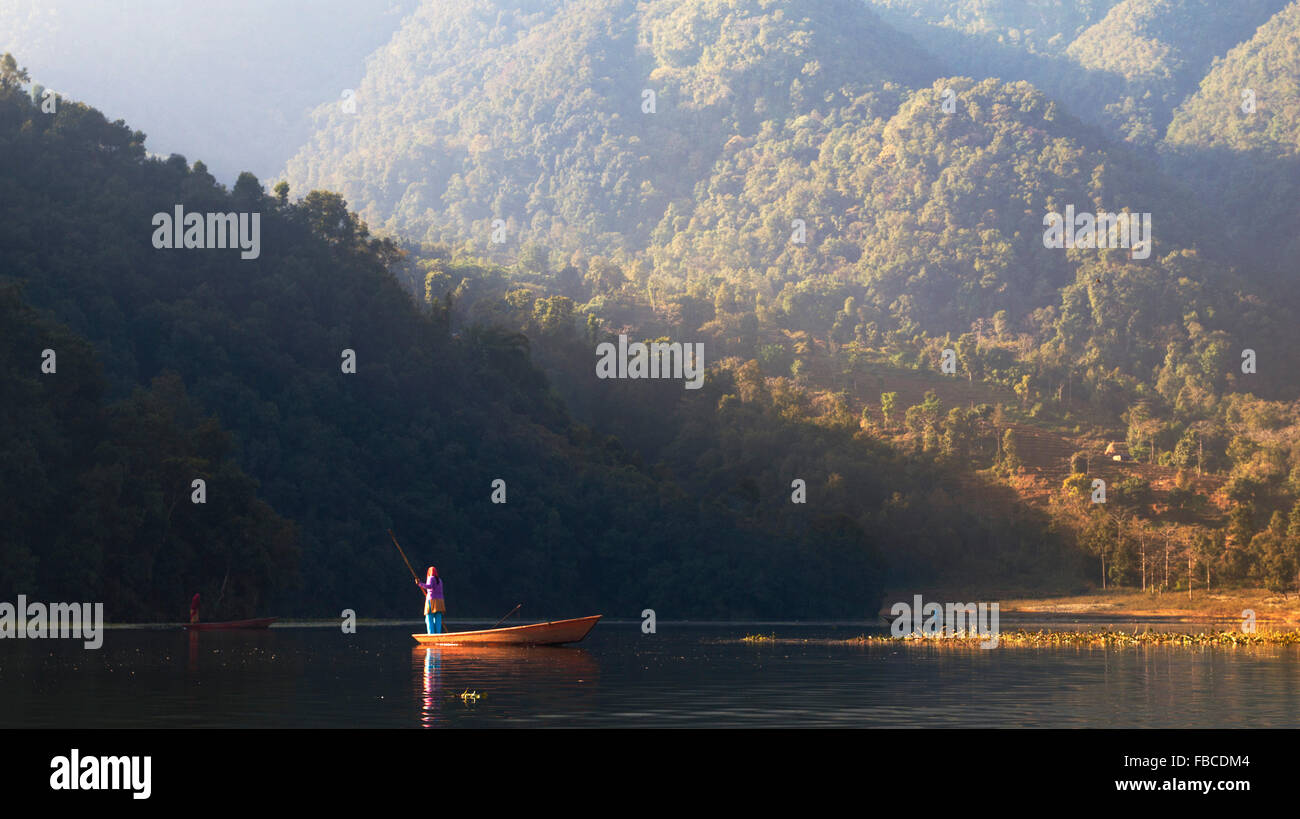 Nepalese woman poling boat Phewa Lake, Pokhara Nepal - Stock Image