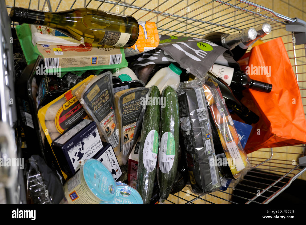 A full supermarket trolley at Aldi's supermarket with food and wine products in packaging and Aldi bags Wales - Stock Image