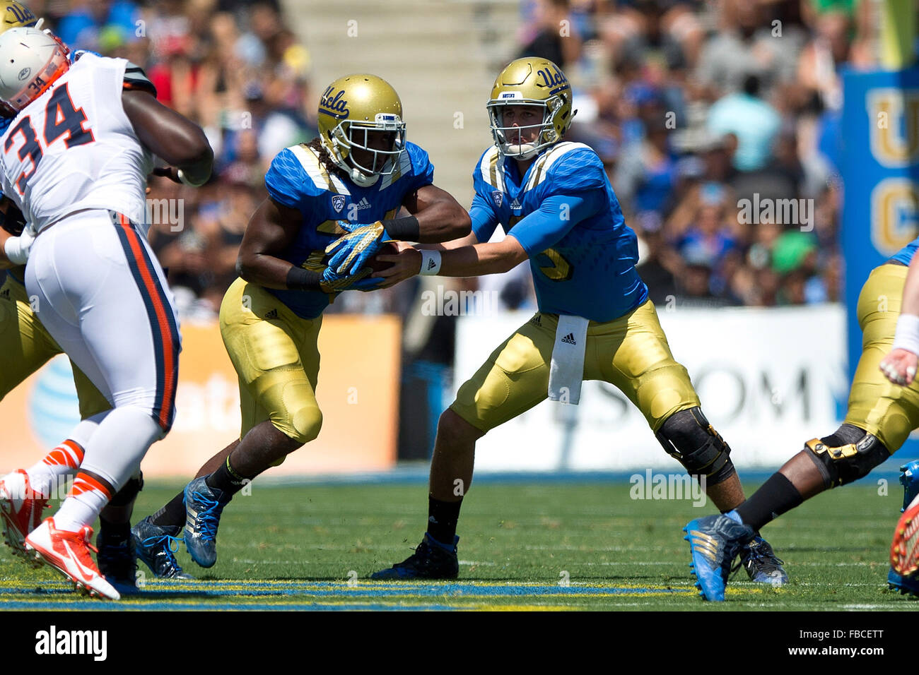 Quarterback Josh Rosen #3 of the UCLA Bruins hands off to running back Paul Perkins #24 during the first quarter - Stock Image