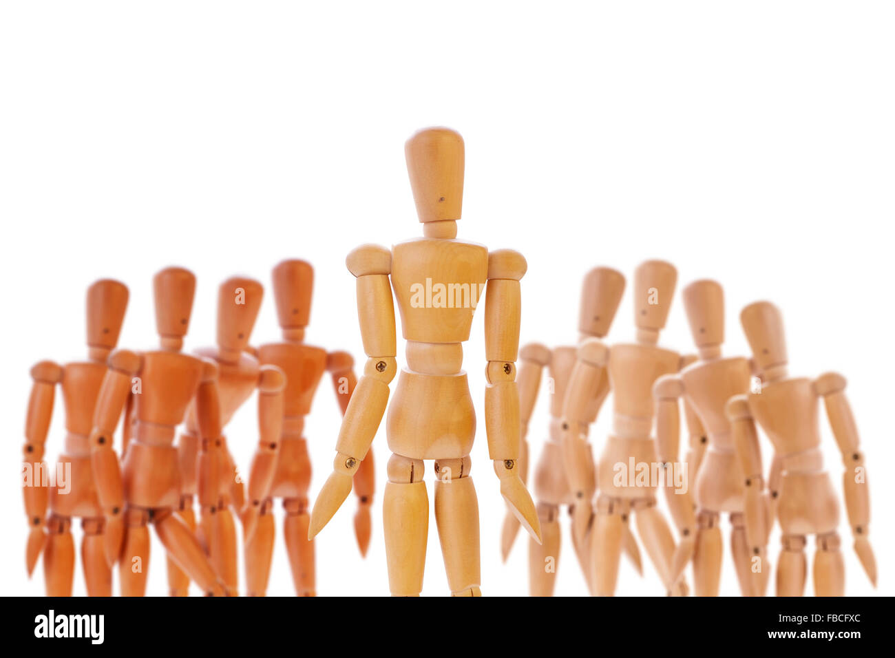 Wooden dummy character standing between two different colored teams. Isolated on white. - Stock Image