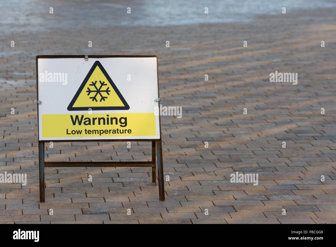 'Warning Low temperature' sign alerting pedestrians to icy slippery surface - Stock Image