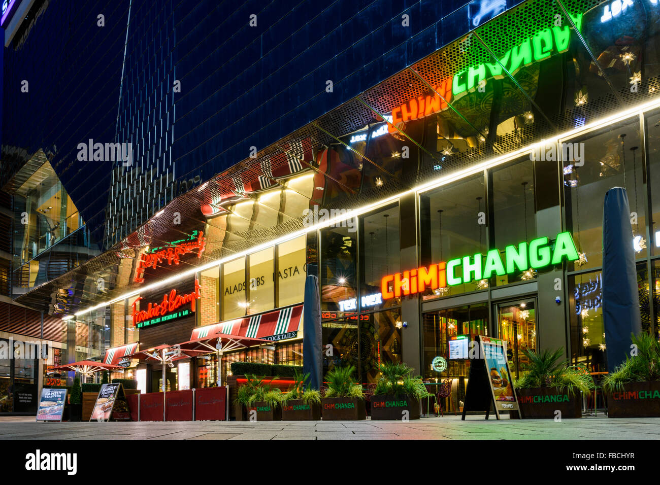 Night view of Chimichanga Mexican restaurant and Frankie and Bennys outside the Highcross shopping centre in Leicester Stock Photo