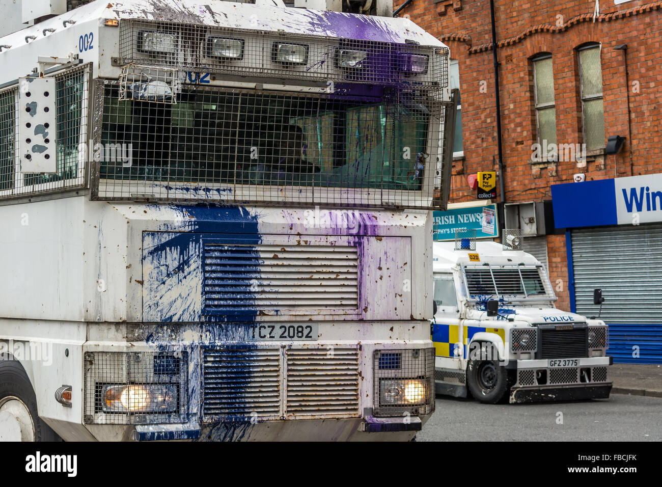 PSNI water cannon vehicle attacked by Irish Republican rioters with paint bombs in Belfast. - Stock Image