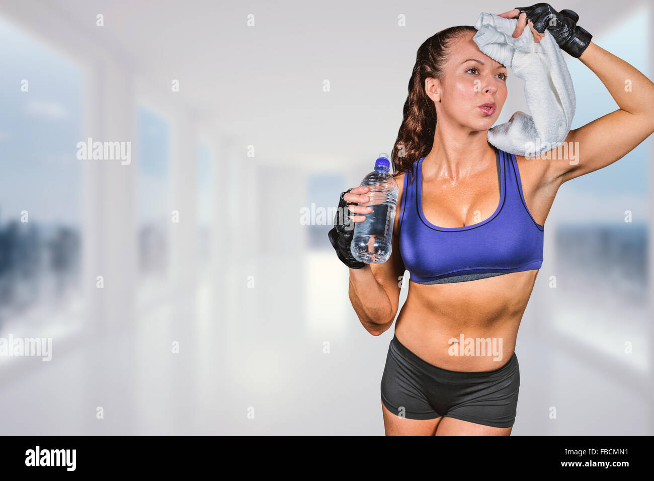 Composite image of exhausted woman wiping sweat while holding water bottle - Stock Image
