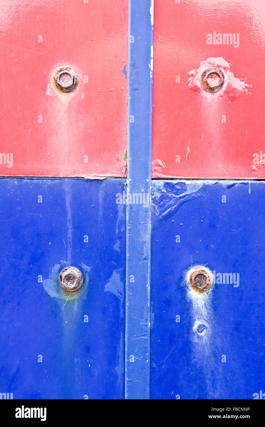 Red and blue metal surfaces with rusted bolts - Stock Image