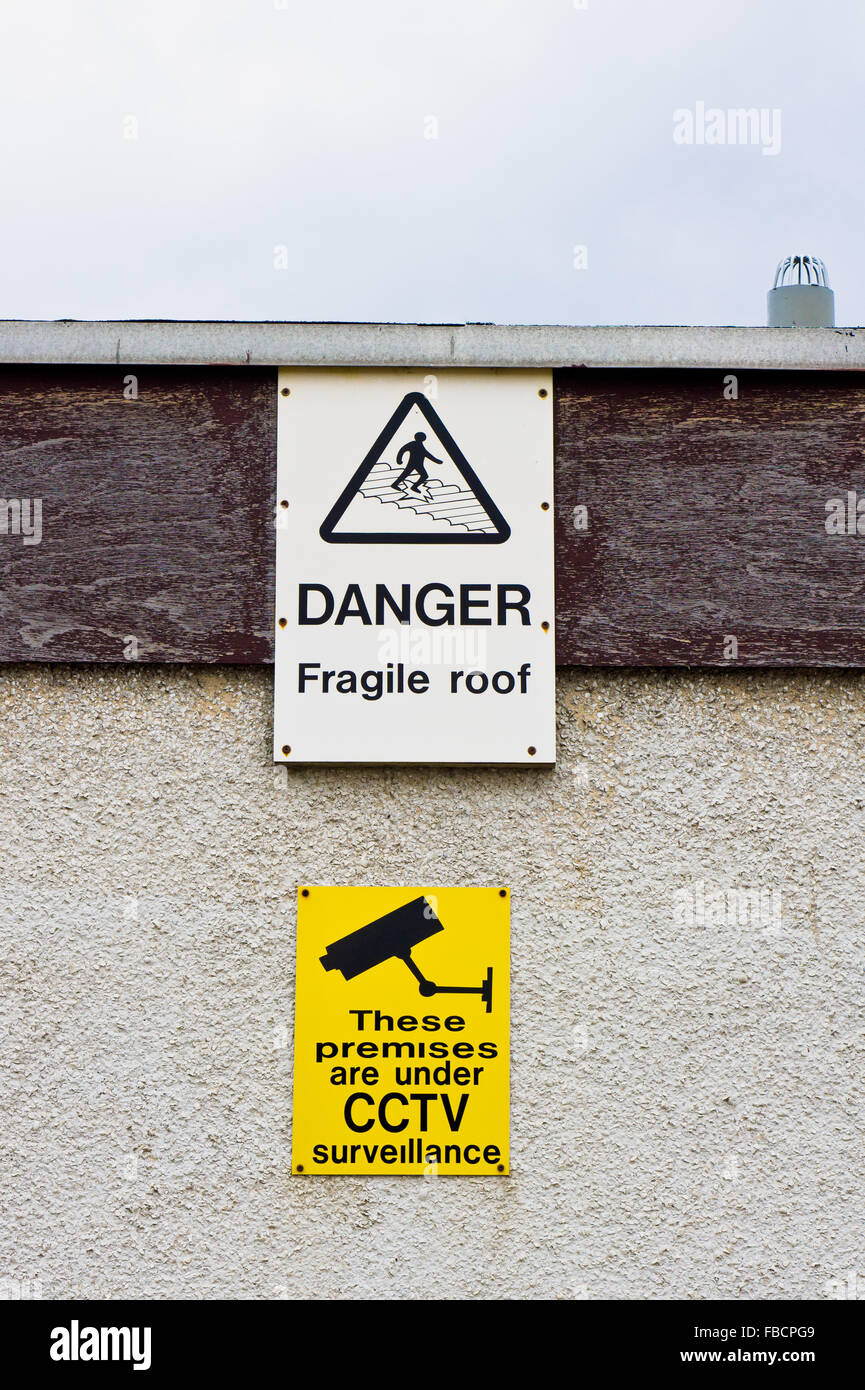 warning signs on a building for a fragile roof and cctv surveillance