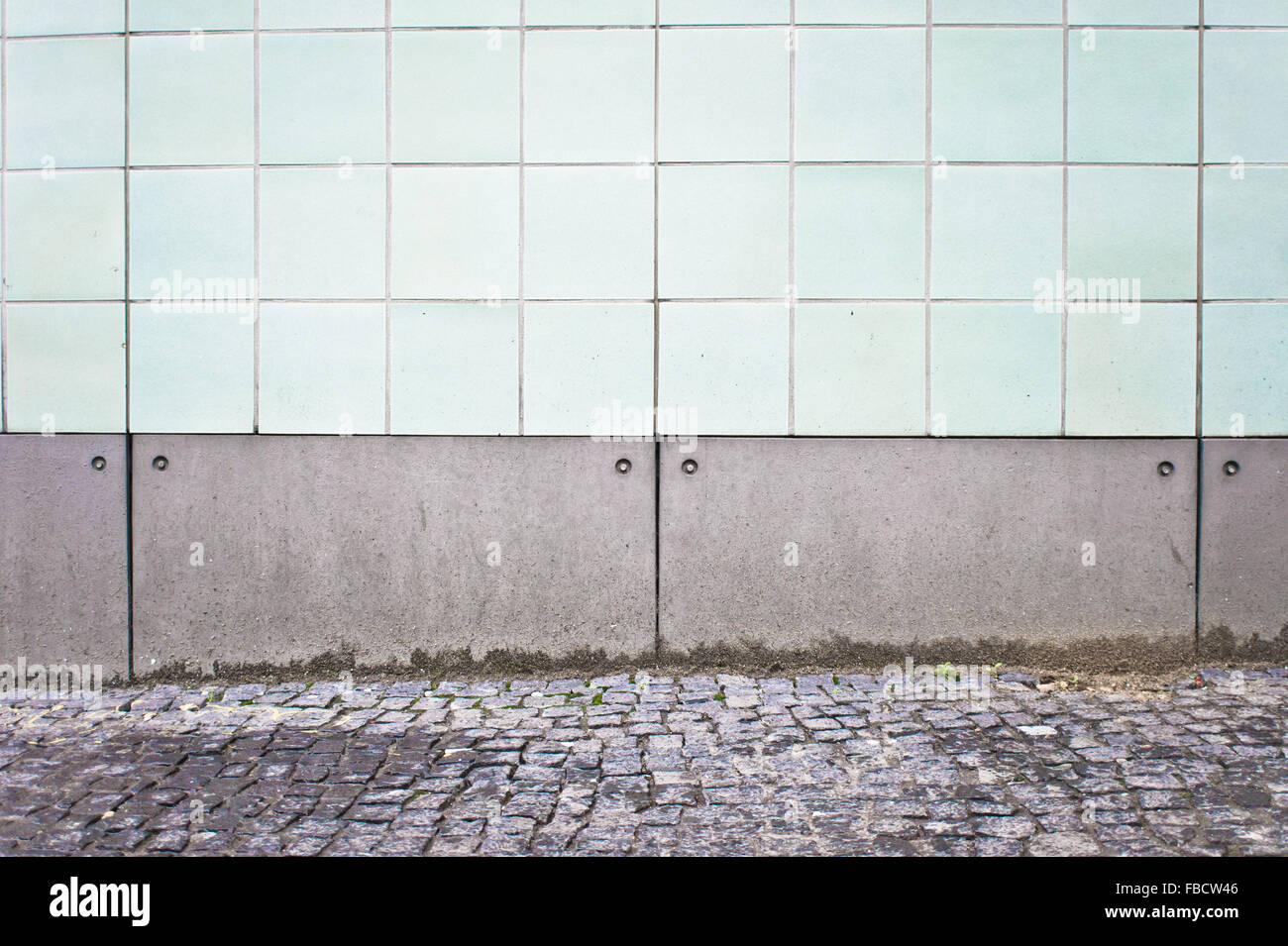Part of a white tiled wall on the exterior of an urban building - Stock Image