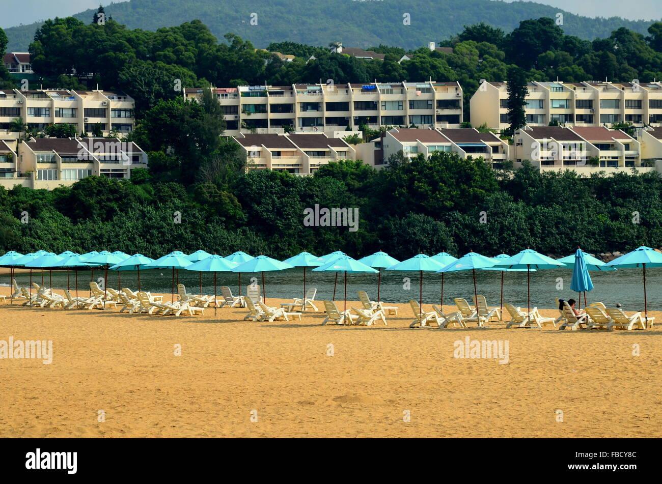 Blue Umbrellas on the beach - Stock Image
