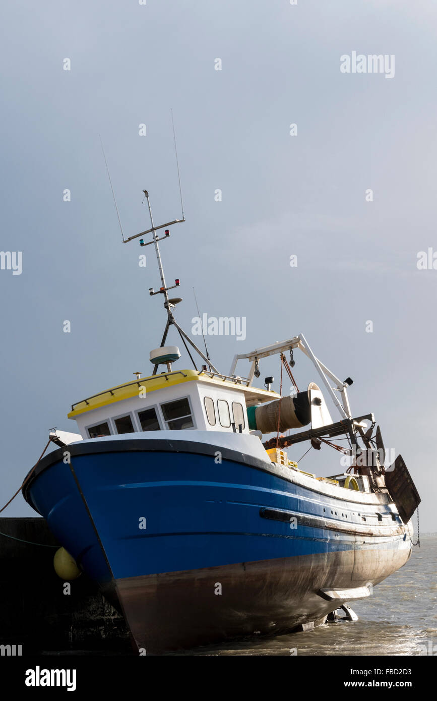 A side-lit moored fishing boat at low tide at Leigh on Sea, Essex - Stock Image