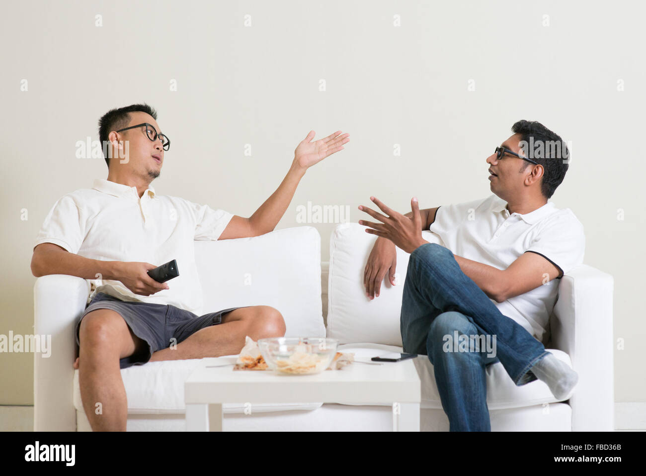 Men arguing. Two male friend disagree to each other and having argument at home. Multiracial people friendship. - Stock Image