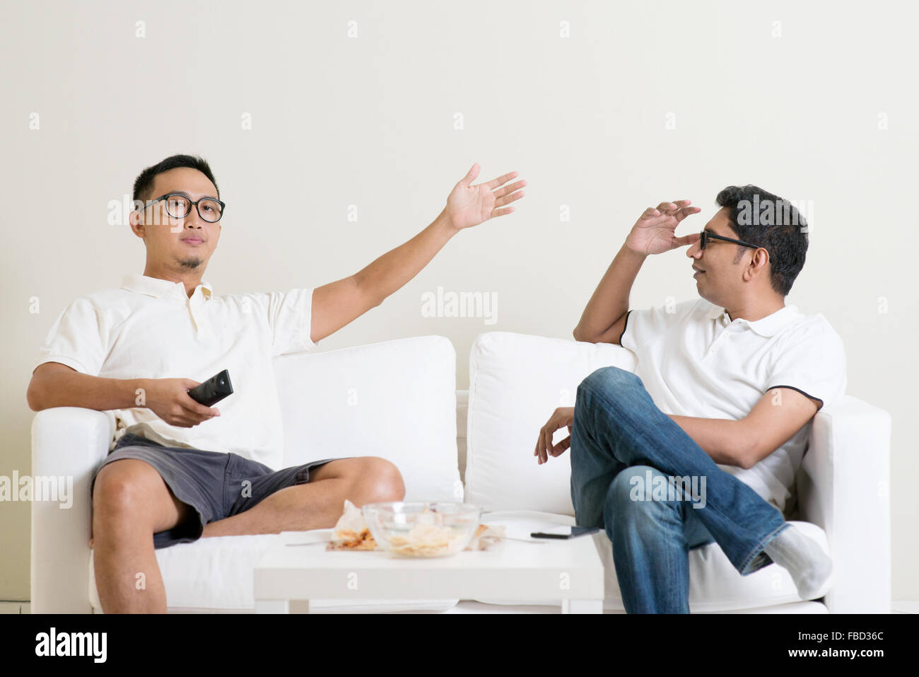 Men arguing. Two male friend having argument at home. Multiracial people friendship. - Stock Image