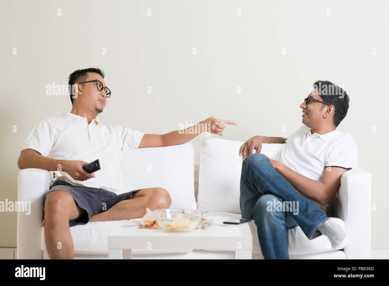 Men arguing. Two middle aged male friend having argument at home. Multiracial people friendship. - Stock Image