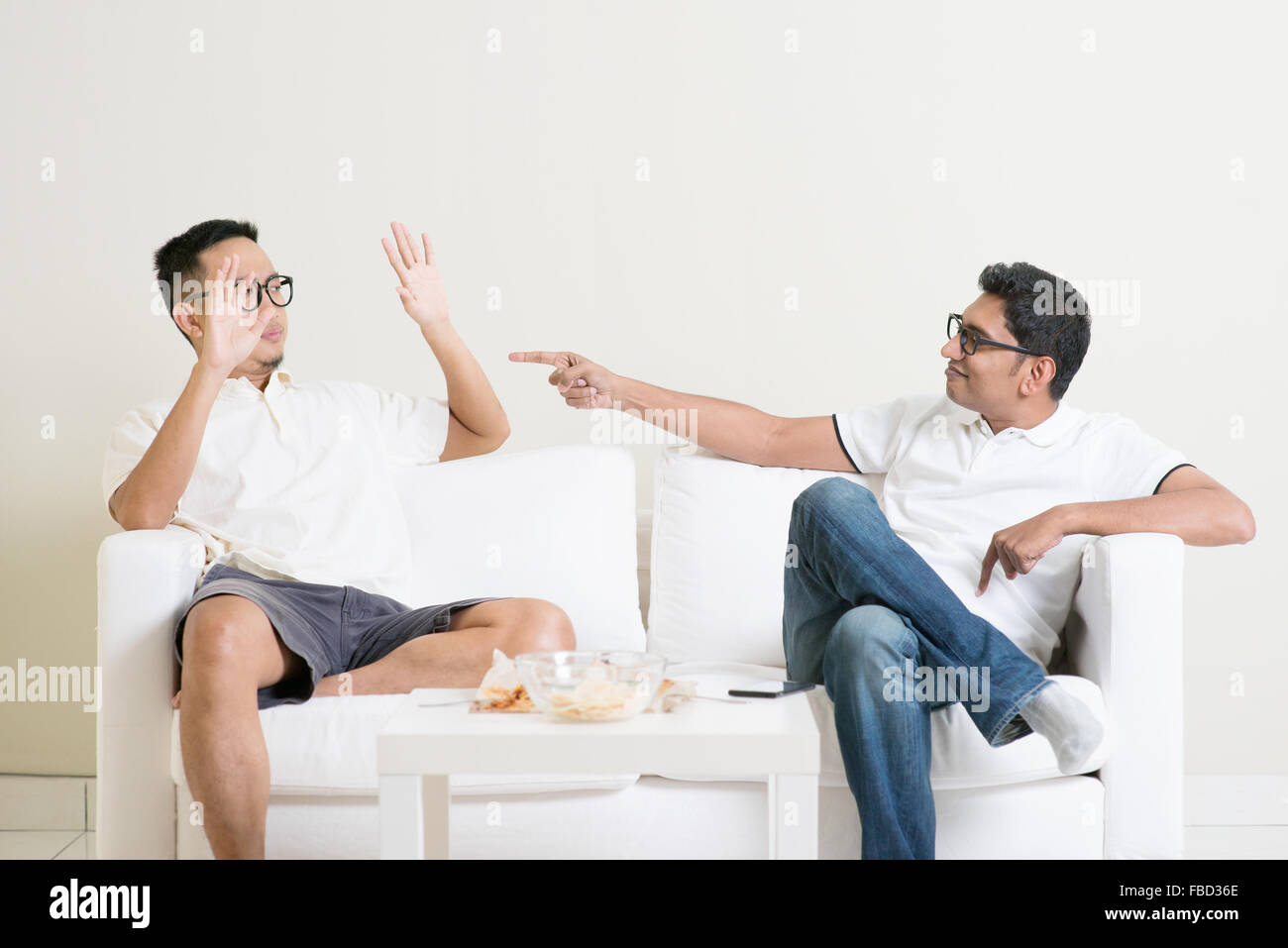 Men arguing. Two young male friend having argument at home. Multiracial people friendship. - Stock Image