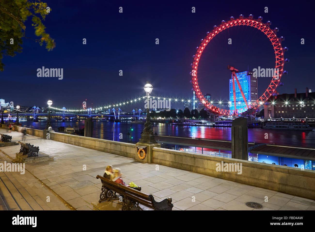 London eye, ferris wheel, illuminated in red in the night and Thames river docks view - Stock Image