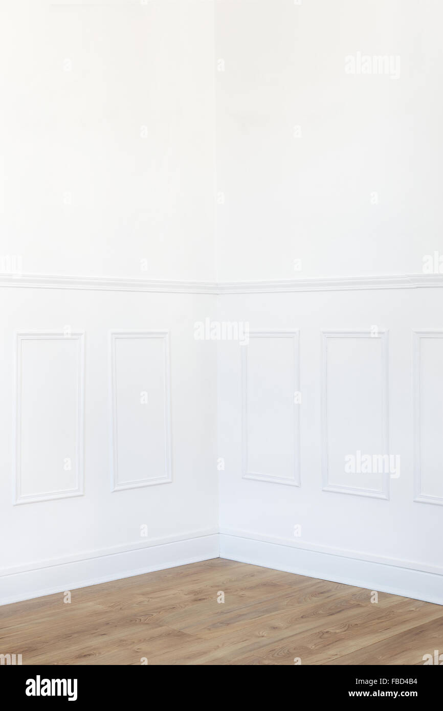 Empty white room corner with parquet floor and wood trimmed wall - Stock Image
