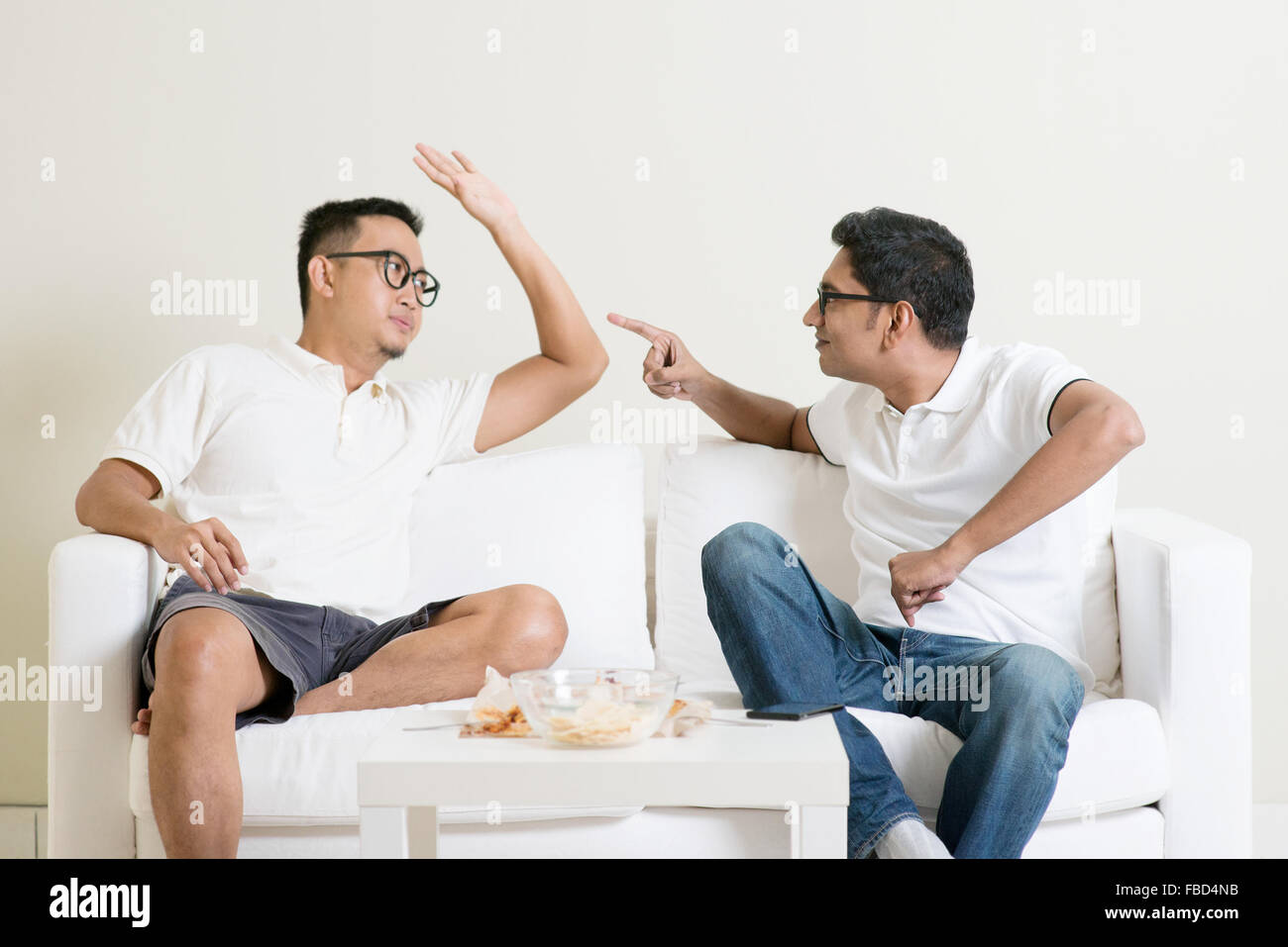 Men talk concept. Two young male friend gathering, chatting and arguing at home. Multiracial people friendship. - Stock Image