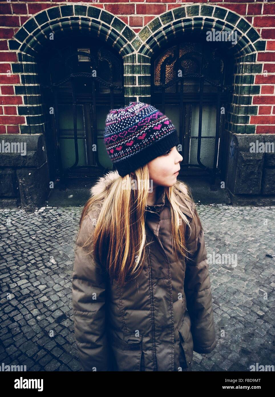 Girl In Warm Jacket Standing On Sidewalk - Stock Image