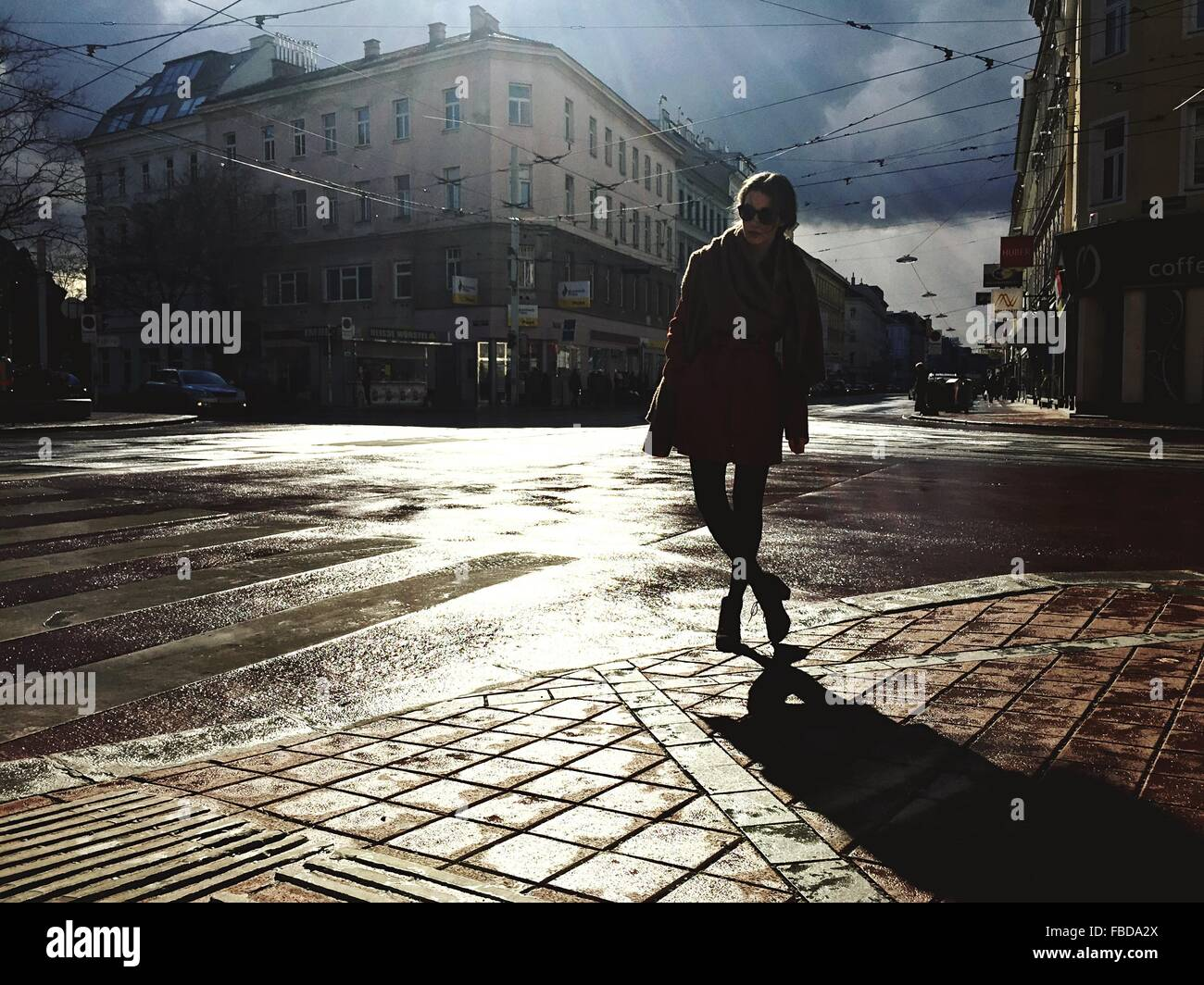 Woman Standing On Wet Street In City - Stock Image