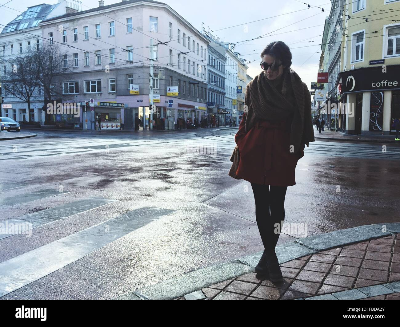 Young Woman Standing On Wet Street In City - Stock Image