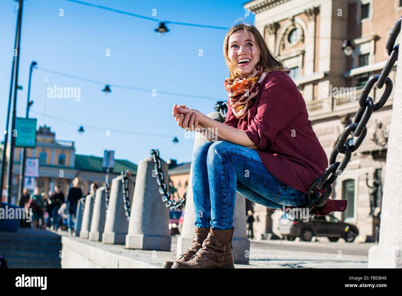 Young Woman Sitting On Chain At Sidewalk - Stock Image