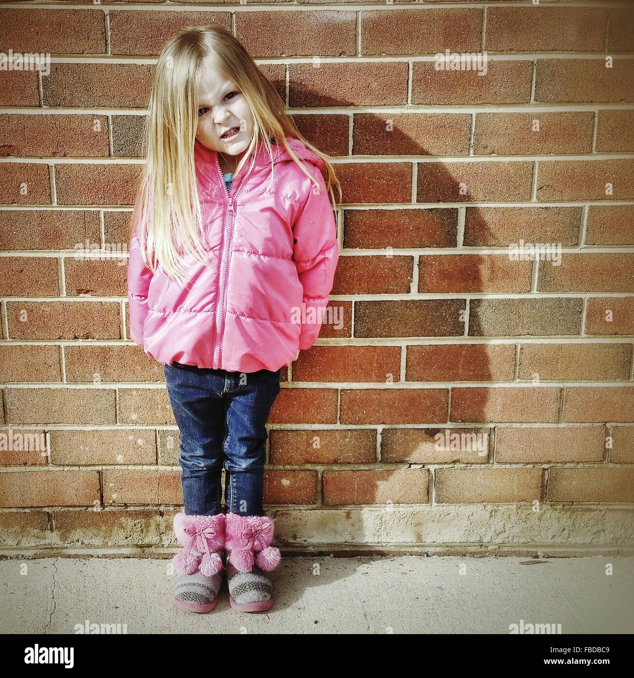 Portrait Of Small Girl Making A Face While Standing Against Wall - Stock Image