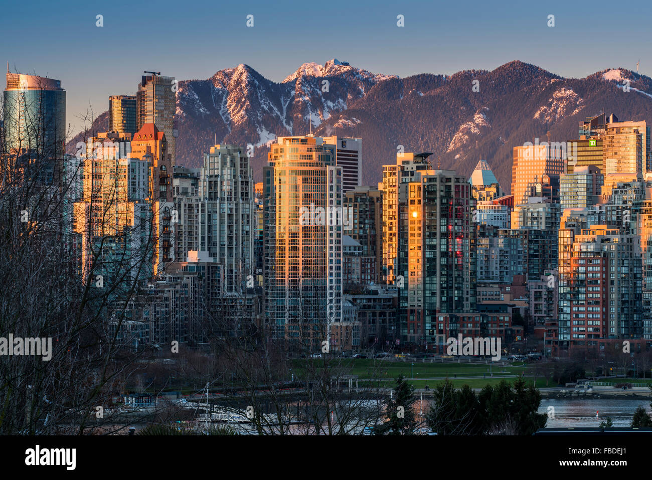Downtown skyline with snowy mountains behind at sunset, Vancouver, British Columbia, Canada - Stock Image