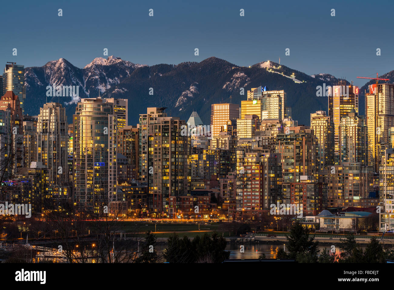 Downtown skyline with snowy mountains behind at dusk, Vancouver, British Columbia, Canada - Stock Image