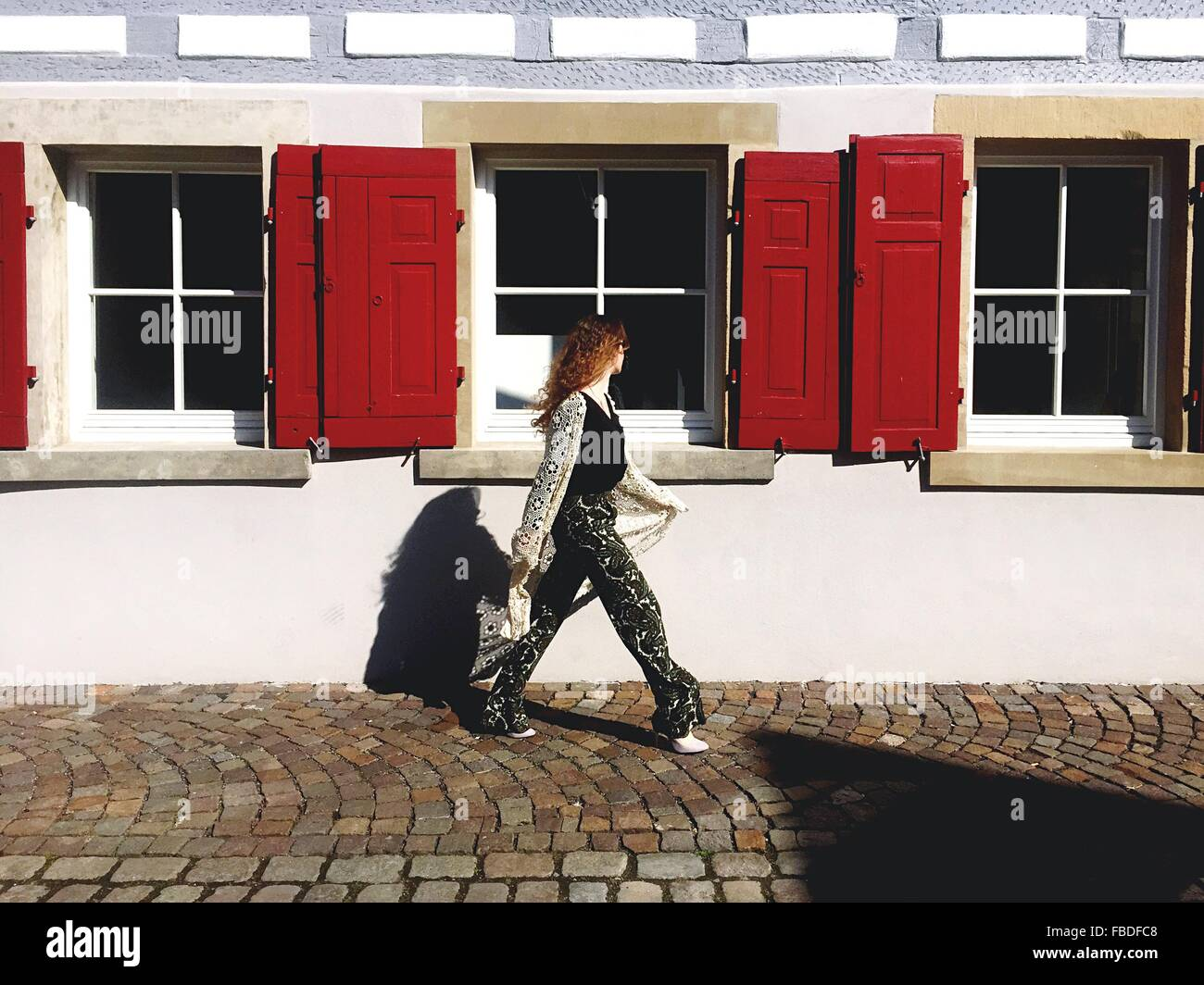 Woman Walking On Street Against Building - Stock Image