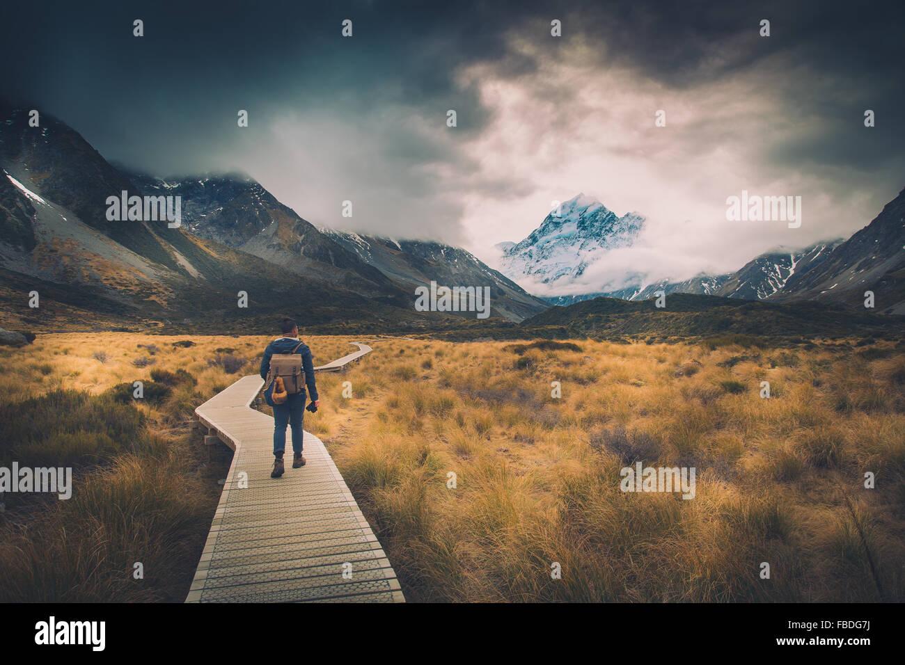 Man Walking On Path To Mountains - Stock Image