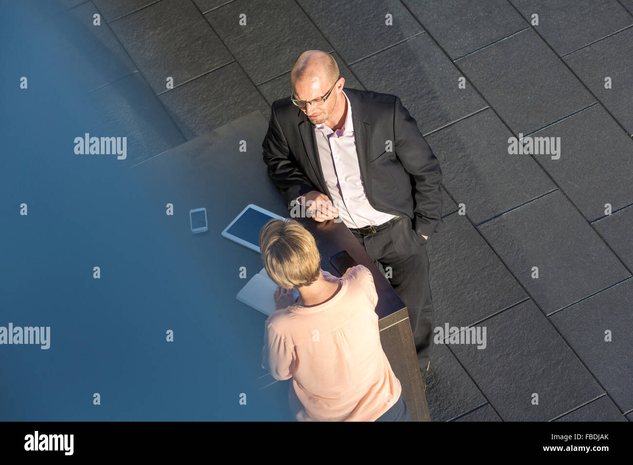 Business women and man discussing on bar table, elevated view - Stock Image